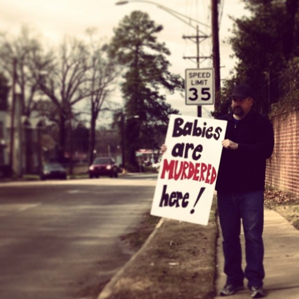 Mike Anderson holds a sign in front of Hope Medical Group, informing the public that babies are murdered there.